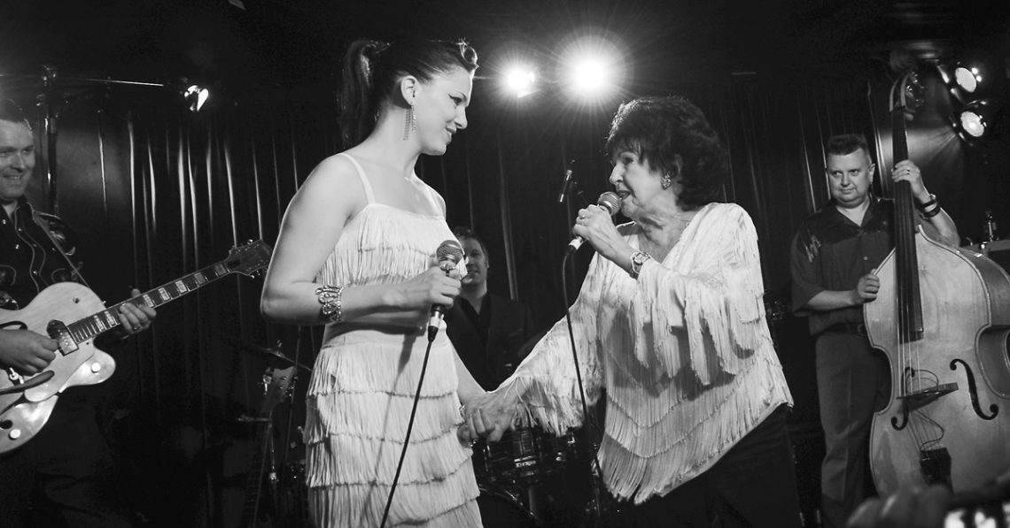 Imelda May and Wanda Jackson holding hands on stage at a gig